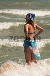 A girl stands in front of the blue soft waves of the sea. A young beautiful girl on a sea beach talk