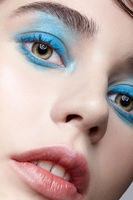 Closeup macro portrait of female face. Woman  with unusual beauty makeup. Girl with perfect skin, green pistachio colour eyes and blue shadows make-up