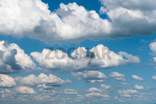 horizontal background of flat anvil-like cumulus clouds in blue sky over Lake Constance