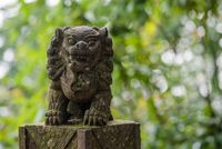 Lion stone statue against trees