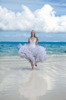 young beautiful woman in a dress of the bride runs on waves of the sea