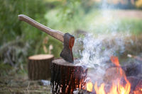 Axe in tree stump and campfire