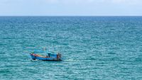 Blue fishing boat traveling along the Gulf of Thailand