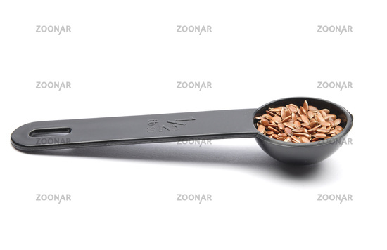 Leinsamen in Dosierlöffel auf weißem Hintergrund - Linseed in measuring spoon on white background