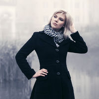 Young fashion woman in classic black coat walking in a fog outdoor
