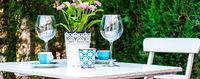Panorama table setting with a wine glasses, cups and flowers in a pot