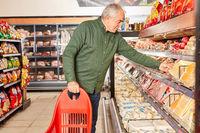Senior als Verbraucher beim Einkaufen am Kühlregal