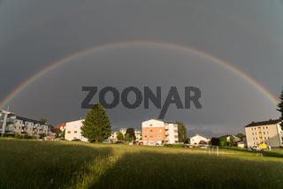 doppelter geschlossener Regenbogen leuchtet bei Gewitter