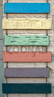 Blank rustic sign hanging on chains against old wall