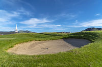 Golf course with sand bunker and vibrant fairway under blue sky on a sunny day