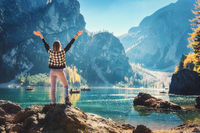 Woman with raised up arms on the coast of Braies lake