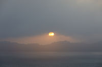 Sun peeking through thick fog rolling in San Francisco during summer sunset.