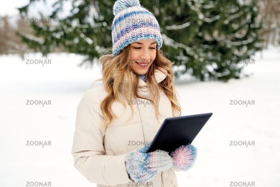 woman with tablet computer outdoors in winter