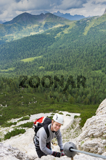 young male climber on a Via Ferrata in the Dolomites of Alta Badia
