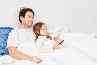 Vater und Tochter im Bett mit Fernbedienung