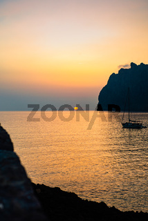 Sunrise Over a Tranquil Bay in the Mediterranean Sea With Mountains and Sailboat