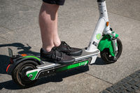 Man riding an electric scooter , escooter or e-scooter of the ride sharing company LIME