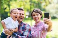 happy family taking selfie at summer park