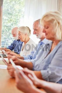 Senioren mit Tablet in einem Computerkurs