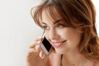 close up of smiling woman calling on smartphone