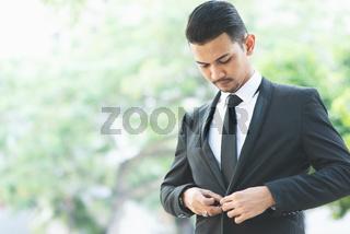 Asian businessman button his suit