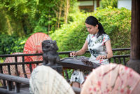 Woman playing Guzheng traditional chinese music instrument