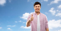 happy young man showing thumbs up over blue sky