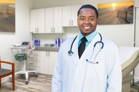 African American Male Doctor Standing In Office