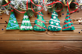 Handmade rustic felt Christmas tree decorations as background on wooden table, place for text.