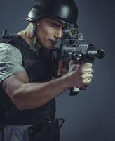 recreation player wearing protective helmet aiming pistol ,black armor and machine gun