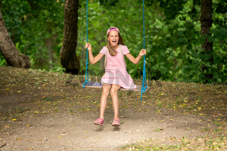 Laughing girl on a tree swings