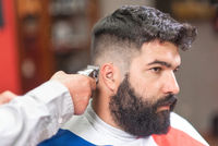 Handsome bearded man, getting haircut by barber, with electric trimmer at barbershop.