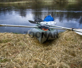 kayaks moored on shore of pond in grass in spring.