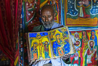 priest of the rock church Mikael Mellehayzengi showing the book Miracles of Maria, Ethiopia