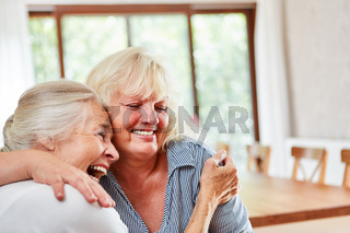 Lachende Seniorin umarmt glücklich eine Freundin
