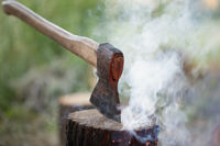 Axe in tree stump and smoke from fire