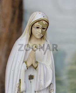 Statue einer Betenden mit weißem Umhang und teilweise abgeblätterter Farbe