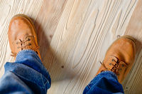Carpenter feet in work boots standing on wooden floor. Place for text