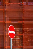 Red one way street sign in front of scaffolding