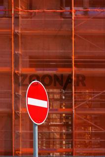 Rotes Einbahnstraßenschild vor Baugerüst