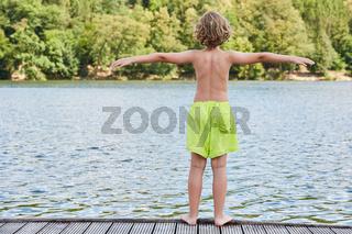 Kleiner Junge auf einem Steg am Badesee