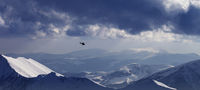 Off-piste slope for heliskiing and helicopter in evening mountains