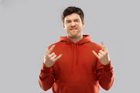 young man in red hoodie showing rock sign
