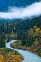 A mountain river surrounded by colorful autumn trees and low clouds