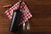 Horizontal High angle view of a red wine bottle on a red and white checkered napkin