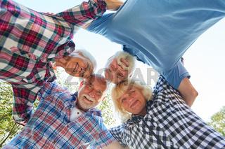 Senioren stehen im Kreis zusammen