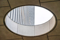 Close up of circular skylight with view of the concrete building exterior wall