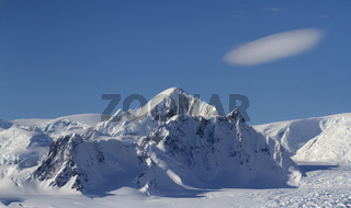 Mount Shackleton and clouds above it in a blue bright sky on the Antarctic Peninsula on a winter day