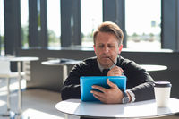 Worried man with tablet in cafe