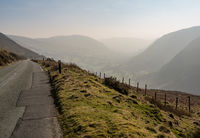 Narrow road besides misty valley in North Wales